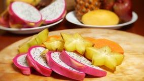 Экзотические плоды на таблице плод 4k, карамболы и дракона, папапайя, маракуйя, отрезок плода в части, вращает на a сток-видео