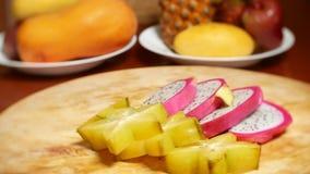 Экзотические плоды на таблице 4k, карамбола и Dragonfruit, отрезок в части, вращают на разделочной доске сток-видео