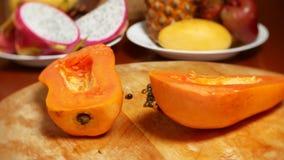 Экзотические плоды на таблице 4k, папапайя, отрезок плода в части, вращают на разделочной доске сток-видео