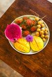 Экзотические плодоовощи на плите: манго, плодоовощ дракона; манго; ананас Стоковые Изображения RF