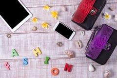 Экзотические сумки snakeskin моды на деревянной предпосылке, взгляд сверху, открытом космосе для текста, smartphone и таблетке с Стоковое фото RF