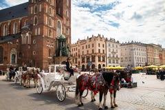 Экипажи лошади на главной площади Rynek Glowny в городке Краков старом стоковые изображения