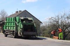 Экипаж отброса муниципальным обслуживанием 2 привратника нагружают отброс в мусоровоз Экологичность и чистота cit стоковые изображения