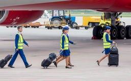 Экипаж самолета в темно-синей форме идя взойти на борт для того чтобы выстрогать Двигатель и шасси самолета на предпосылке Экипаж стоковые фото