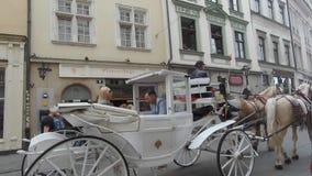 Экипаж со спешкой белых лошадей через старый городок сток-видео