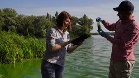 2 эколога берут образцы зеленых водорослей на берег реки береге реки и вписывают данные на планшете сток-видео