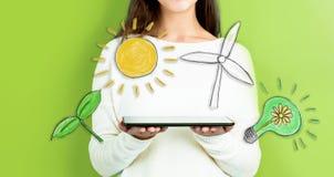 Экологичность при женщина держа таблетку стоковые изображения