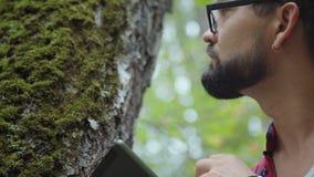 Эколог изучает мох на дереве и пишет данные к планшету акции видеоматериалы
