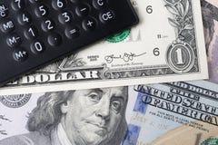 Экономика Америки, бюджет компании, доход от бизнеса и потеря, вклад или финансовая концепция, черный калькулятор на куче доллара стоковые фото
