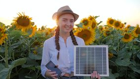Экологически дружелюбная, женская улыбка в подсвеченном держит в черни и солнечной батарее рук отслеживая солнце для того чтобы п видеоматериал