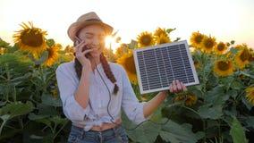 Экологически дружелюбные ресурсы, девушка говорят мобильным телефоном и держат панель солнечных батарей около поля солнцецветов,  акции видеоматериалы