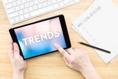 Экран касания пальца с словом тенденций с клавиатурой и бумагой дальше стоковое фото