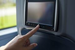 Экран мультимедиа женщины касающий на шине Стоковые Фото