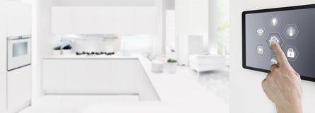 Экран планшета умного касания руки домашней автоматизации цифровой с символами на внутри помещения предпосылке комнаты и кухни, з стоковое изображение rf