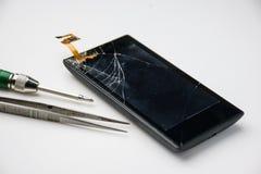 Экран сломанный мобильным телефоном с инструментом стоковое фото