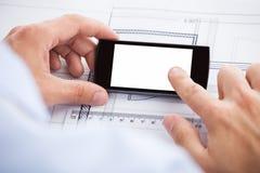 Экран smartphones архитектора касающий над bluepri Стоковое фото RF