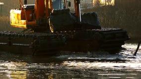Экскаваторы очищают и углубляют русло реки на заходе солнца сток-видео
