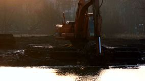 Экскаваторы очищают и углубляют русло реки на заходе солнца видеоматериал