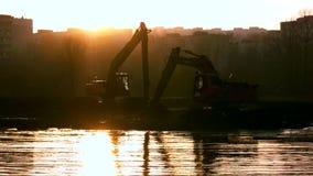 Экскаваторы очищают и углубляют русло реки на заходе солнца акции видеоматериалы