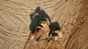 Экскаватор выкапывает песок и нагрузки оно в тележку