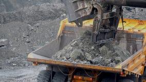 Экскаватор заполняет самосвал Крупный план ковшевого экскаватора нагружает камни в тело самосвала на минировании или конструкцию  стоковое изображение