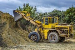 Экскаватор затяжелителя колеса при backhoe разгржая песок на eathmoving работает в карьере строительной площадки стоковое изображение