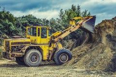 Экскаватор затяжелителя колеса при backhoe разгржая песок на eathmoving работает в карьере строительной площадки стоковое изображение rf