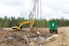 Экскаватор и кабины для работников лесохозяйства на валке леса прокладывают курс Стоковые Фотографии RF