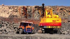 Экскаватор нагружает камень в тяжелом грузовике в граните минирования карьера видеоматериал