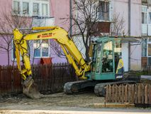 Экскаватор на месте строительства дорог перед старым жилым домом стоковое фото