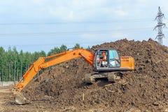 Экскаватор на строительной площадке нагружает почву стоковое изображение
