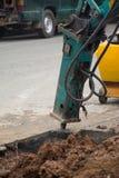 Экскаватор ломая и сверля конкретную дорогу стоковое фото rf