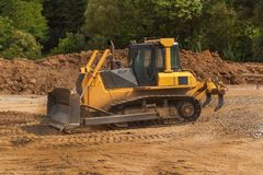 Экскаватор работая на строительной площадке Желтый бульдозер конструкции на работе Конструкция новой дороги Стоковое фото RF