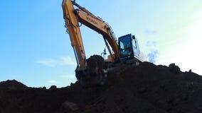 Экскаватор Hyundai нижнего взгляда выкапывает землю с большим ведром акции видеоматериалы