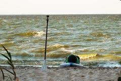 Экспедиция стоит вверх paddleboard, затвор и доска маленького глотка на береге, стоковая фотография rf