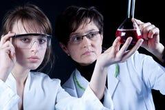 экспериментируя женские научные работники стоковые изображения