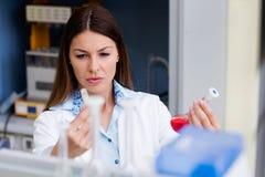 Эксперимент по приведения в исполнение ученого женщины в исследовательской лабаратории стоковое фото rf