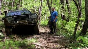 Экспедиционное полученное SUV вставило в лесе и пробовать выйти через ворот акции видеоматериалы
