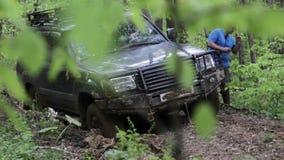 Экспедиционное полученное SUV вставило в лесе и пробовать выйти через ворот сток-видео