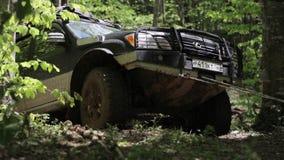 Экспедиционное SUV пробуя преодолеванную трудную область через ворот сток-видео