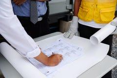 эксплуатацинный инженер пишет план строительства на бумаге Стоковые Изображения