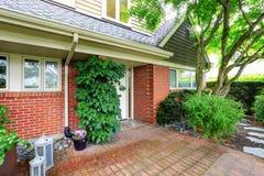 Экстерьер дома кирпича с двором перед входом плиточного пола Стоковое Изображение RF