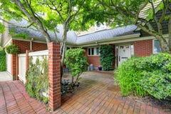 Экстерьер дома кирпича с двором перед входом плиточного пола Стоковая Фотография