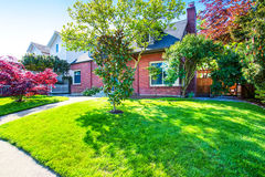 Экстерьер дома красного кирпича с колодцем держал передний сад Стоковое Изображение RF