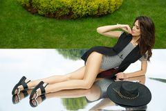 Элегантная, красивая и стильная молодая дама представляет в природном парке стоковые фотографии rf