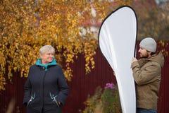 Элегантная пожилая женщина представляя к фотографу, ассистентскому держа рефлектору Стоковая Фотография