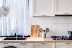 Элегантная черная раковина в современной роскошной кухне с белой деревянной мебелью Стоковая Фотография RF