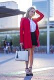 Элегантное белокурое положение женщины в улице нося красную куртку стоковые фотографии rf