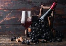 Элегантное стекло красного вина с темными виноградинами и бутылкой вина внутри винтажного деревянного бочонка на темной деревянно стоковые фото