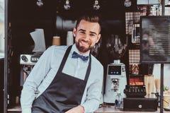 Элегантное barista ждет клиентов на его собственном небольшом coffeeshop стоковая фотография